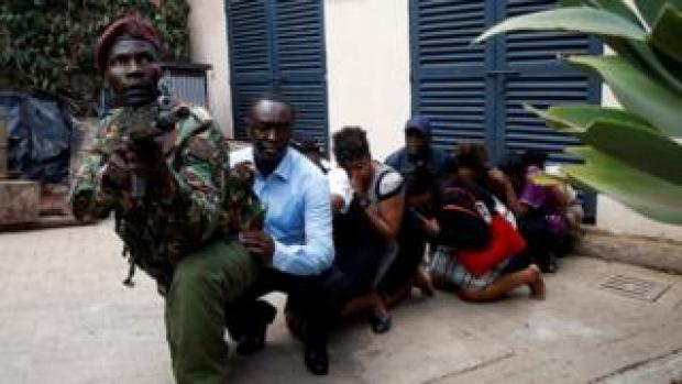 People are evacuated by a member of security forces at the scene where explosions and gunshots were heard at the Dusit hotel compound, in Nairobi, Kenya January 15, 2019.