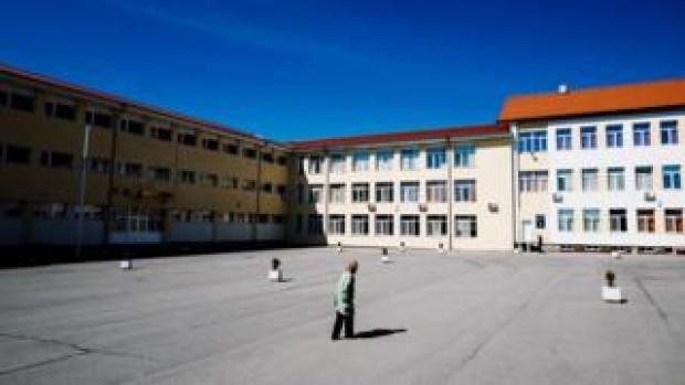 A woman walks towards a building in Bulgaria