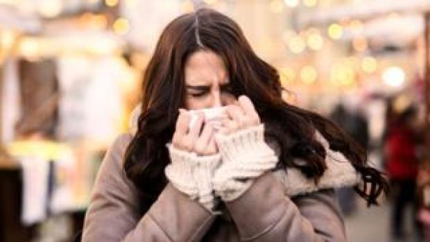 A woman blowing her nose on a tissue
