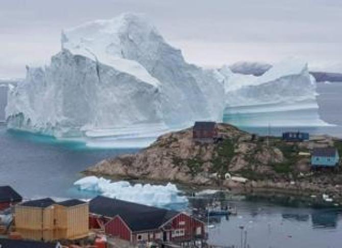 A giant iceberg is seen behind an Innaarsuit settlement, Greenland