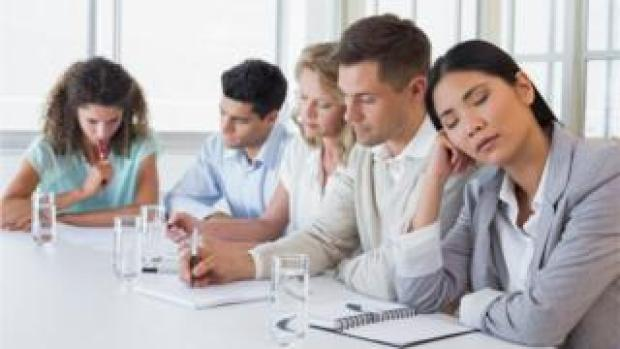 People in meeting, one woman falling asleep