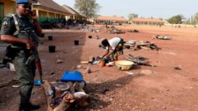 Un policier au téléphone, tenant son arme dans un camp de déplacés des violences communautaires.