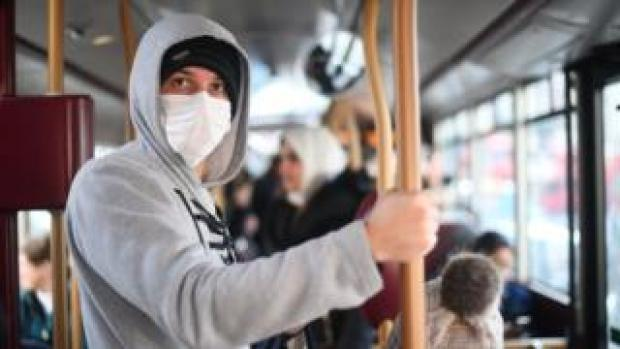 A man wearing a facemask on a bus in London