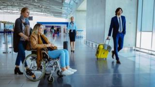 Crowd of people with luggage at international airport - stock photo