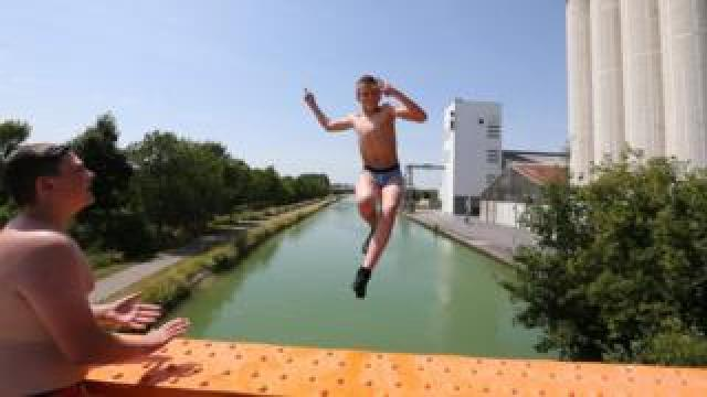 A youngster jumps in Reims canal on June 25, 2019 during a heatwave