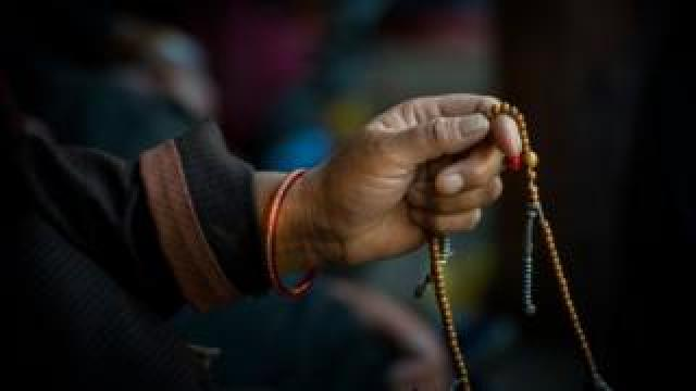 A Buddhist monk holds beads