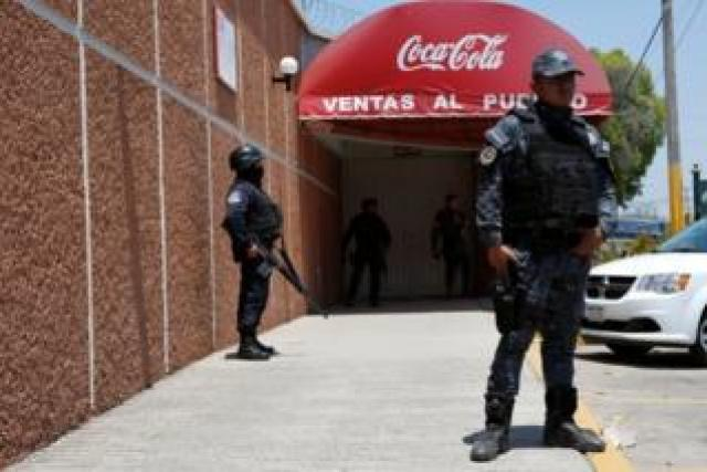 Police officers guard the entrance of the Coca-Cola FEMSA distribution plant after it closes down due to the issues of security and violence during the campaign rally of Independent presidential candidate Margarita Zavala (unseen) in Ciudad Altamirano in Guerrero state, Mexico April 3, 2018.