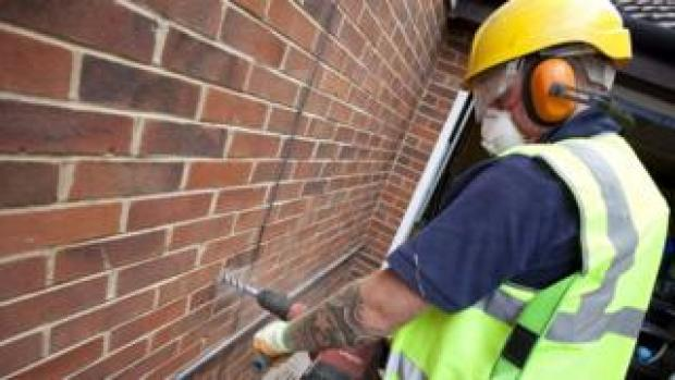 A man installing cavity wall insulation