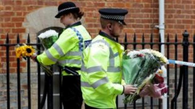 Police officers carry flowers left at the scene of multiple stabbings in Reading