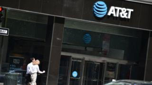 People walk by an AT&T store in New York City, on May 11, 2018.