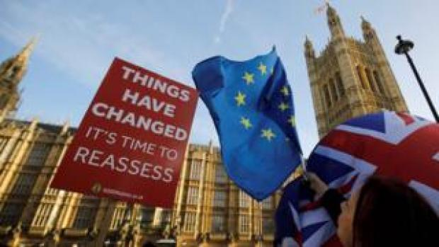 An anti-Brexit placard outside Parliament demands a reassessment of the options, while EU and Union Jacks are waved