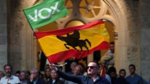 A Vox supporter waves a flag