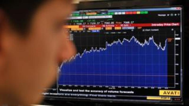 Trader in front of FTSE screen