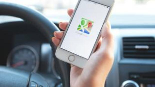 An unidentified woman holds a phone showing a Google Maps icon
