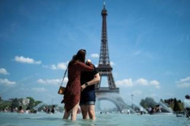 A couple kiss as they cool themselves down in the fountain of the Trocadero esplanade in Paris on June 25, 2019 with the Eiffel Tower on the background