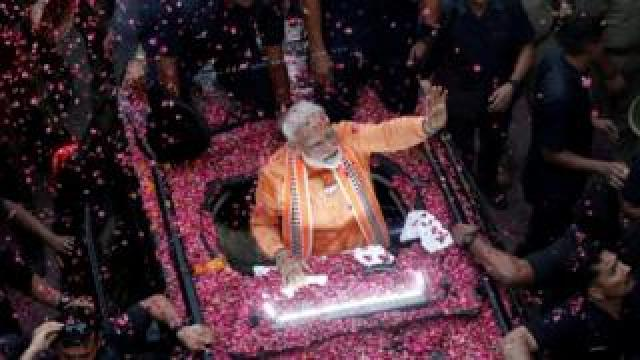 Prime Minister Narendrea Modi waves at supporters during a road show in Varanasi.