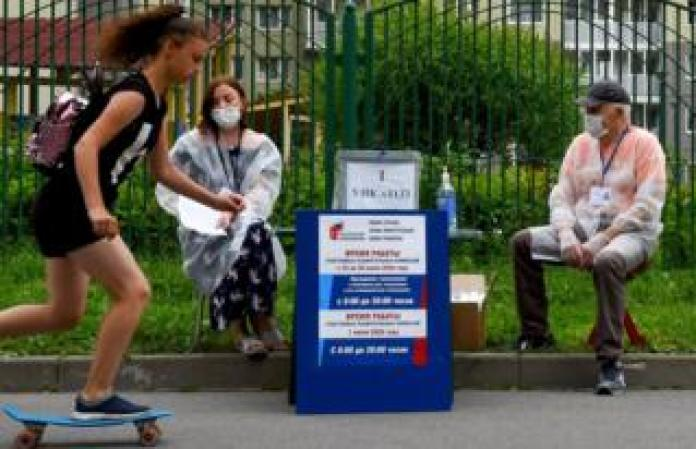 A girl skates her board past members of a local electoral commission wearing face masks