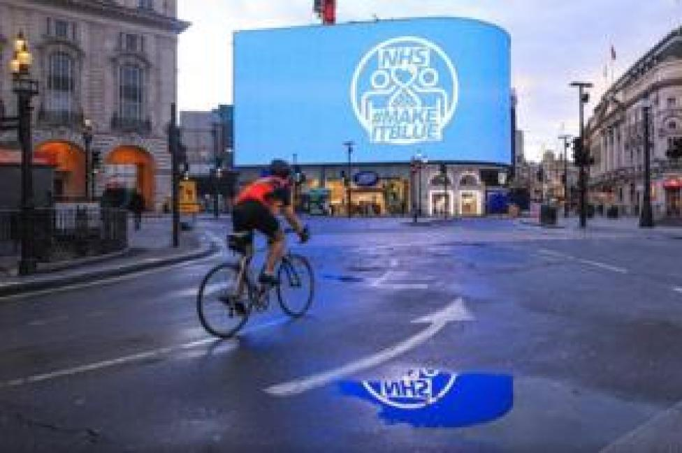 Cyclist in empty Piccadilly Circus with large NHS billboard