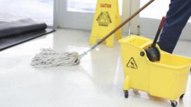 A cleaner with a mop and bucket