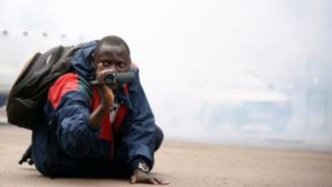 A Uganda journalists with his camera amid tear gas in Kampala, Uganda - Wednesday 11 July 2018