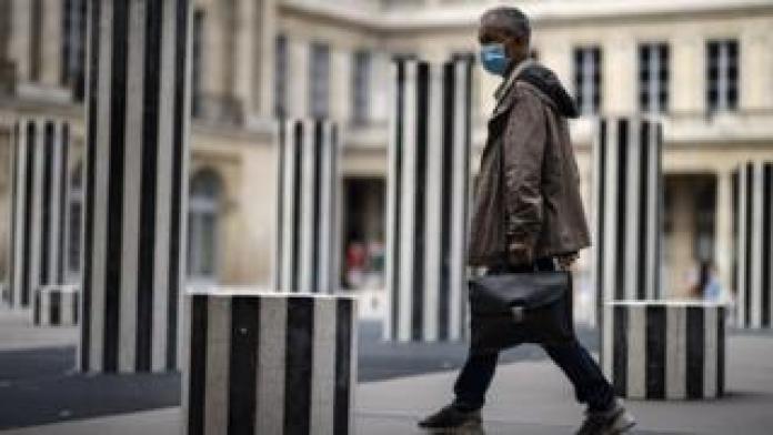man walks through paris art installation