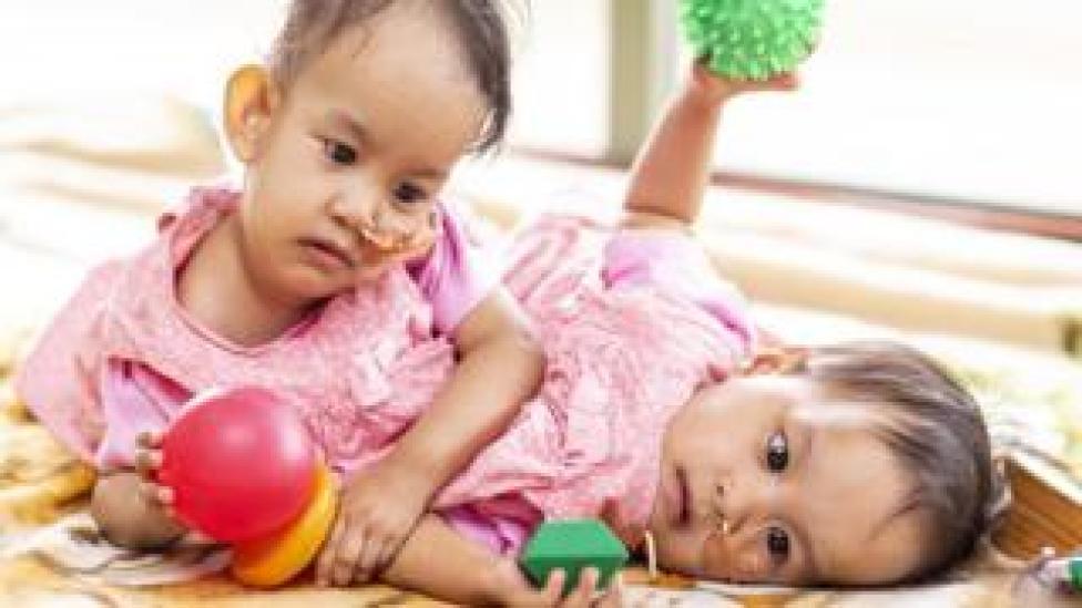 Los gemelos butaneses Nima y Dawa Pelden juegan con juguetes