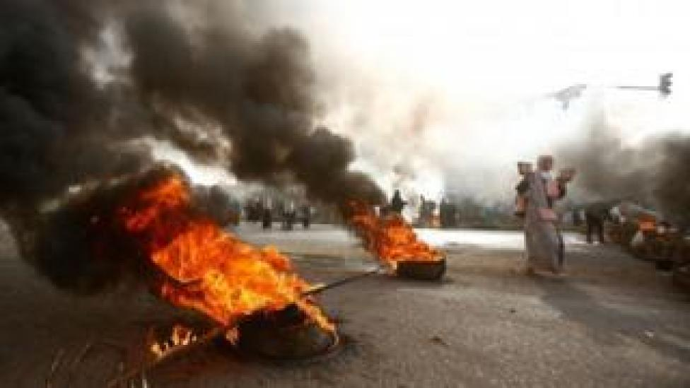 A protesters with pave stones walks past burning tyres in Khartoum, Sudan. Photo: 3 June 2019