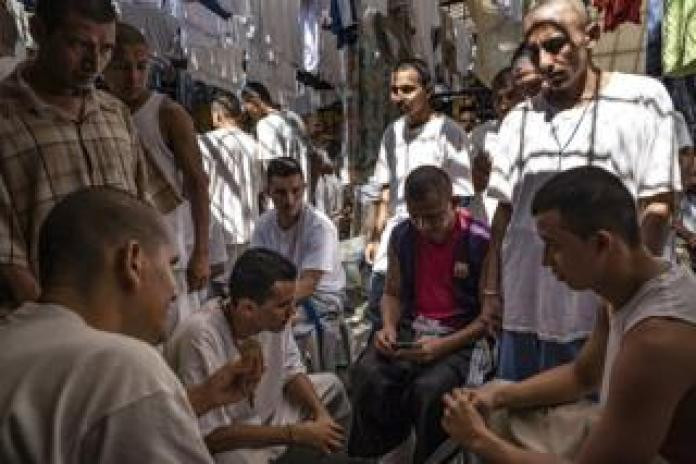 Detainees play cards while others watch at the Chalatenango Penal Center in El Salvador. November 7, 2018.