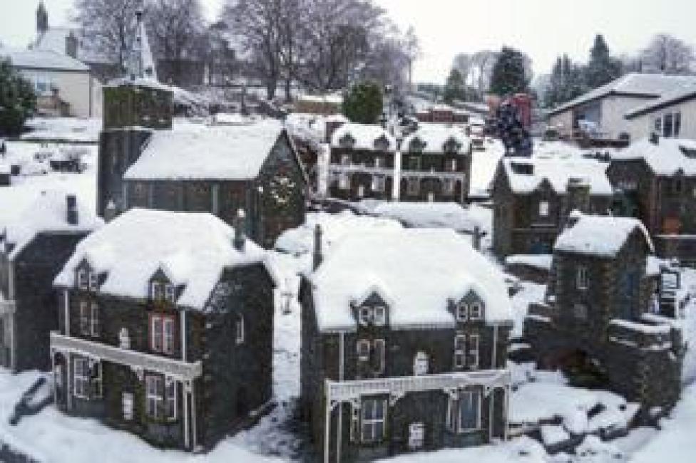 trump Rawson Robinson clears snow from a model village