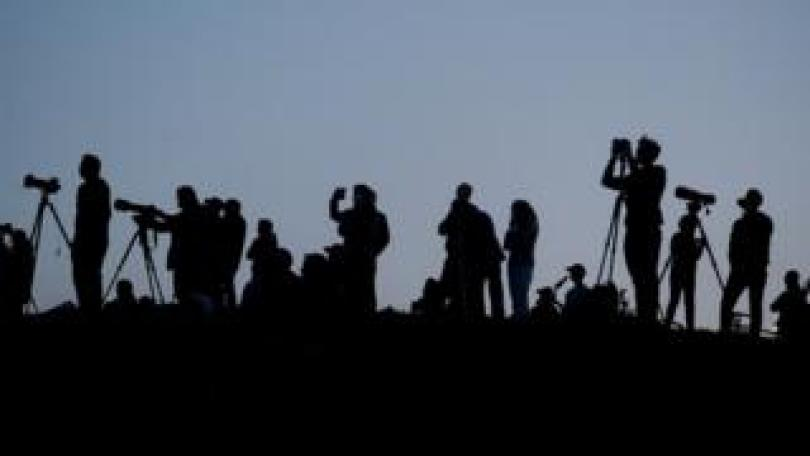 Silhouetted media members and people documenting the full moon, also known as the Supermoon or Flower Moon, over Primrose Hill, are seen in London, Britain