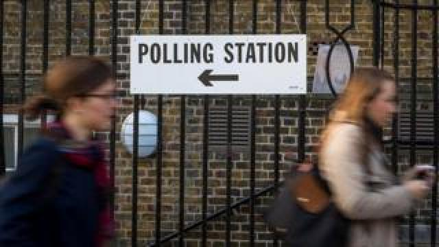 """Women passing a """"polling station"""" sign"""