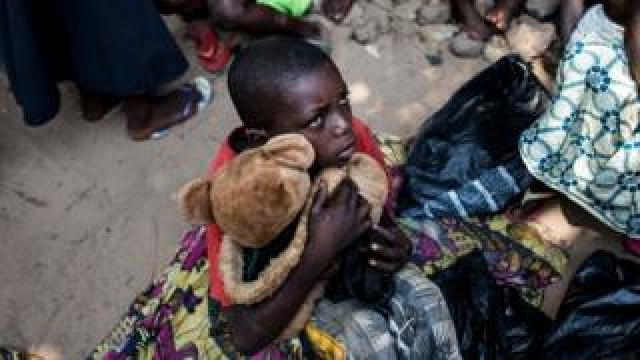 A boy holds his teddy bear as he waits with other Internally Displaced Persons (IDP) for a daily food ration at a camp for people fleeing the conflict in the Kasai Province on June 7, 2017 in Kikwit.
