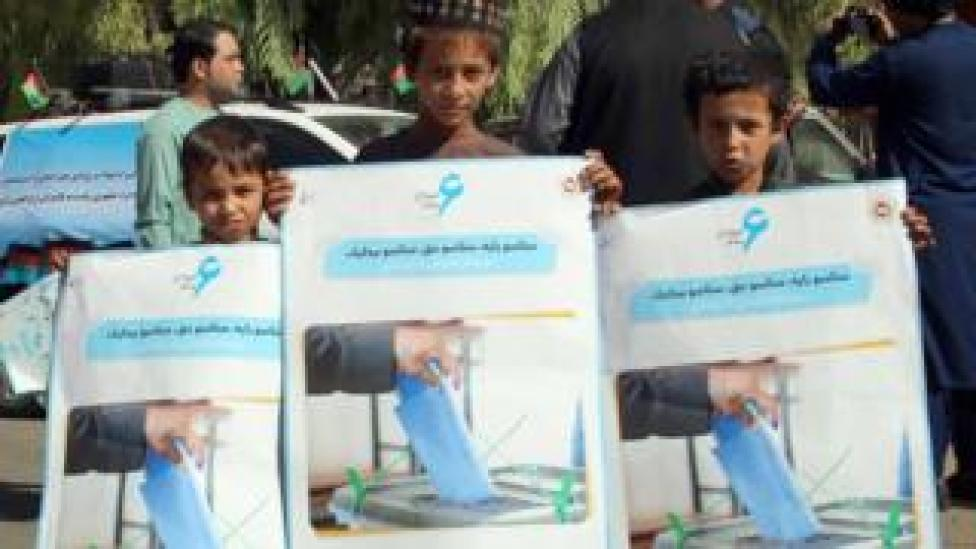 Afghan boys hold posters, featuring the importance of the ballot, distributed by the Afghan Independent Election Commission (IEC) on roads ahead of the Presidential elections in Helmand,