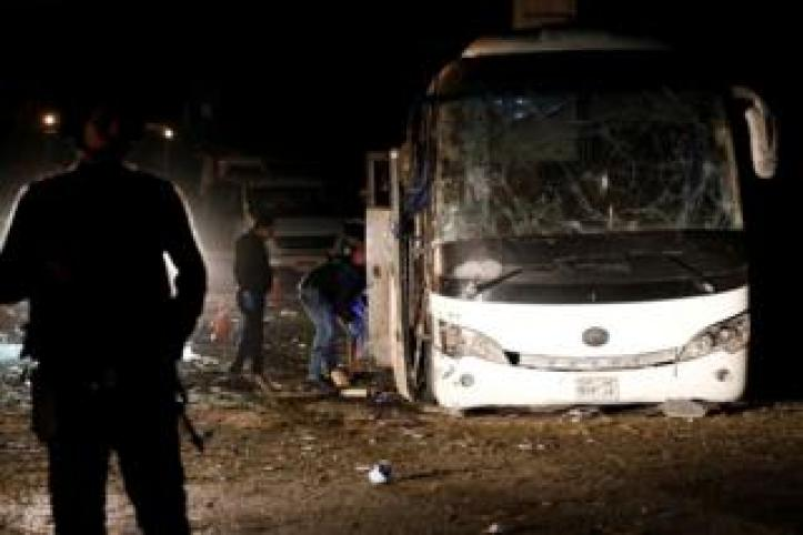 Police officers inspect the scene of a bus blast in Giza, Egypt, 28 December 2018