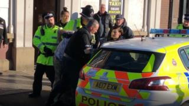 A man is bundled away by police to protect him from an angry crowd after he disrupted a silent tribute with fireworks at a Remembrance Sunday event at the cenotaph in Eccles