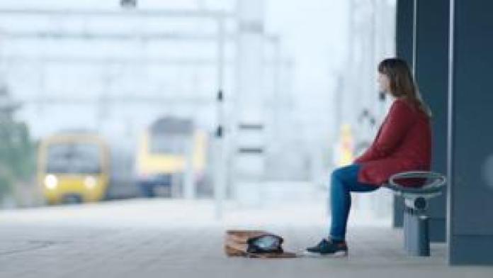 Woman sat on train platform
