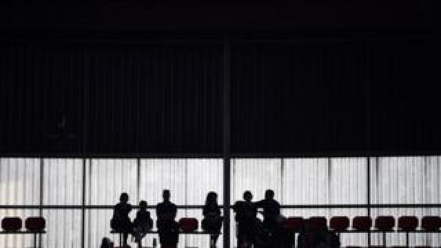 The silhouettes of a group of people are seen in a football stadium.