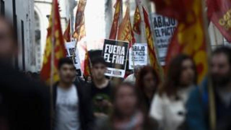 Dozens of protesters march around the Central Bank, in Buenos Aires, Argentina