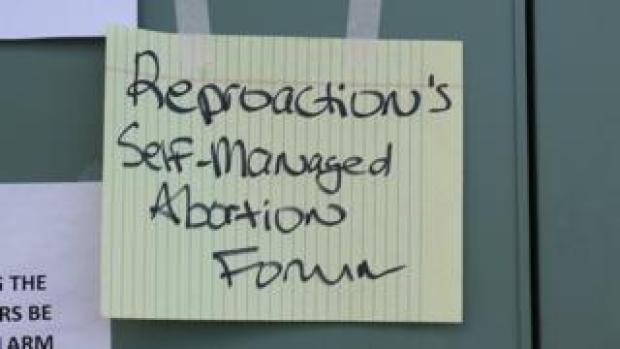 "A sign that reads ""Reproaction's self-managed abortion forum"""