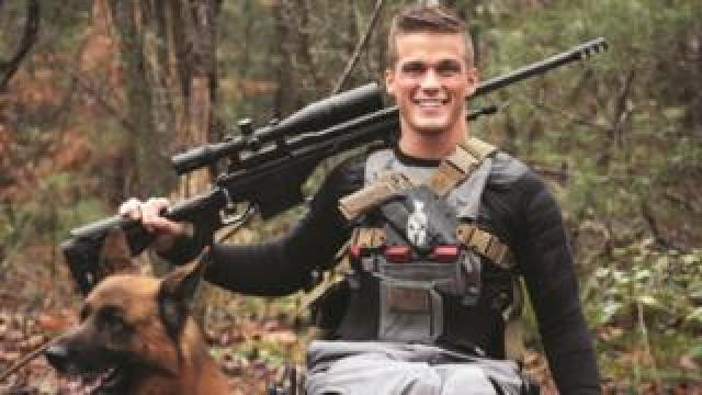 Image of candidate Madison Cawthorn showing him dressed for hunting with large gun and dog (image released by his campaign)