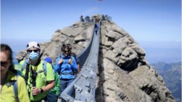 Tourists wearing protective face masks walk on the Peak Walk suspension bridge of Glacier 3000, in Les Diablerets, Switzerland