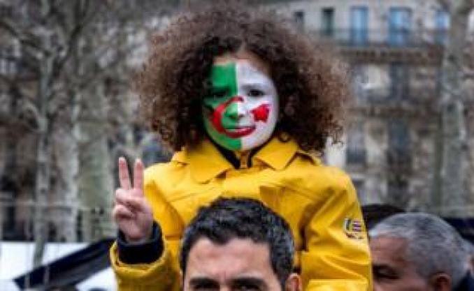 A young girl is seen with an Algerian flag painted on her face sitting on the shoulders of her father during a demonstration against Algerian President Abdelaziz Bouteflika in Place de la République on 17 March 2019 in Paris.