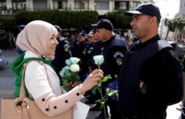 A demonstrator offers a flower to a police officer as teachers and students take part in a protest