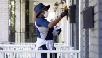 A mail carrier of the United States Postal Service delivers mail in Washington, DC, USA, 18 August 2020