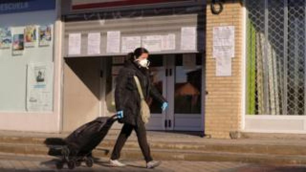 A woman protected with a mask and gloves walks past a public employment office