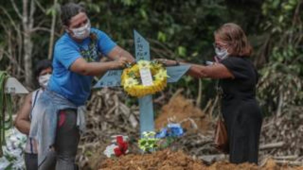 Women lay flowers after a man's funeral in Manaus