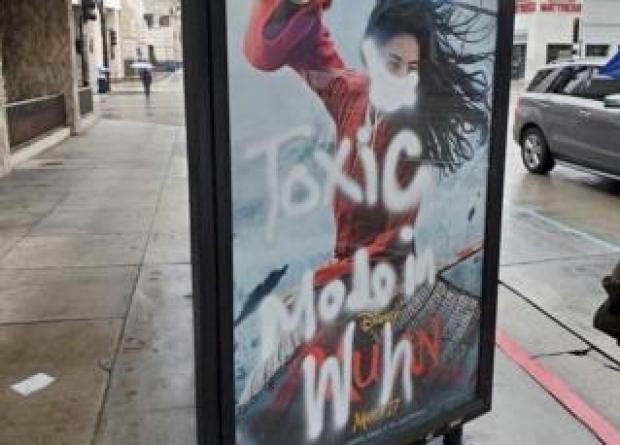 """A Mulan film poster defaced with graffiti - a mask is painted over her face, along with the words """"toxic made in Wuhan"""""""