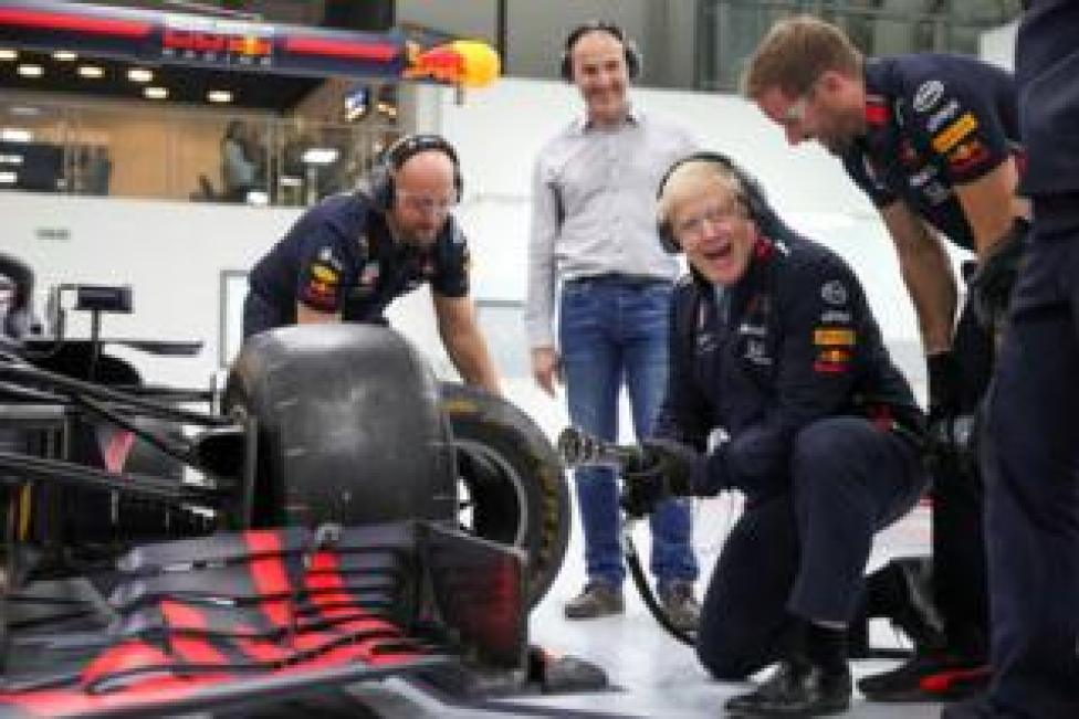 Prime Minister Boris Johnson changes a wheel on a Formula One car during a visit at Red Bull Racing in Milton Keynes