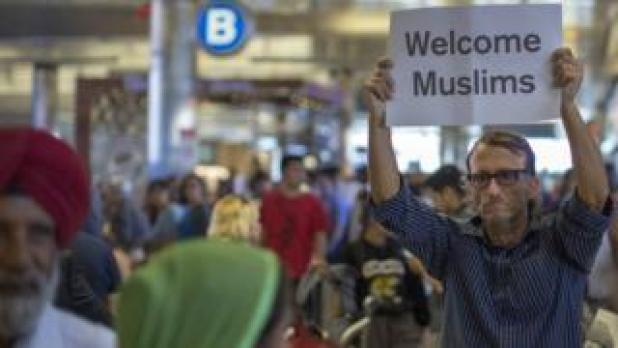 John Wider with a welcome sign for Sikh travellers on the first day of the the partial reinstatement of the Trump travel ban at Los Angeles International Airport (LAX), 29 June 2017