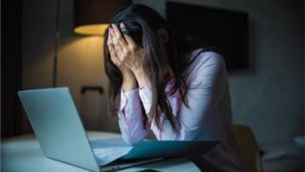 woman with head in hands on laptop